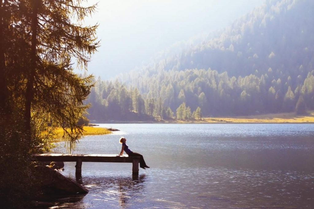 Woman sitting on the dock of a lake contemplating life