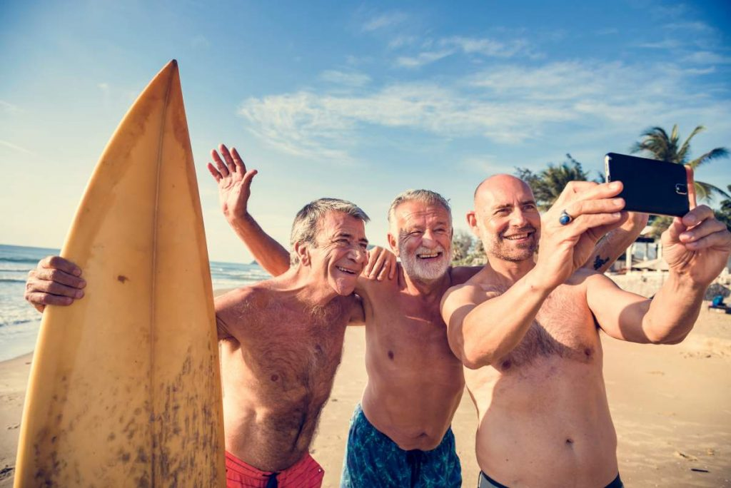 Group of senior men surfing on 2020 holiday