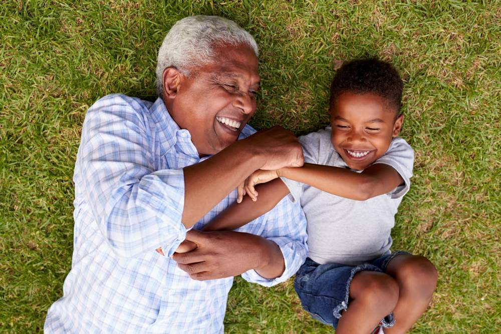 Grandfather and grandson laying down on on the grass having fun
