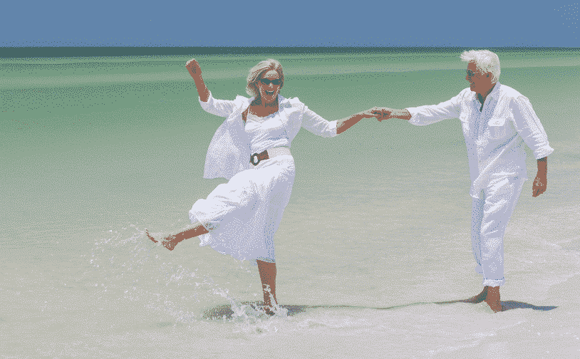 Over 50s Guide to Traveling in Spain: Old couple dancing in the ocean