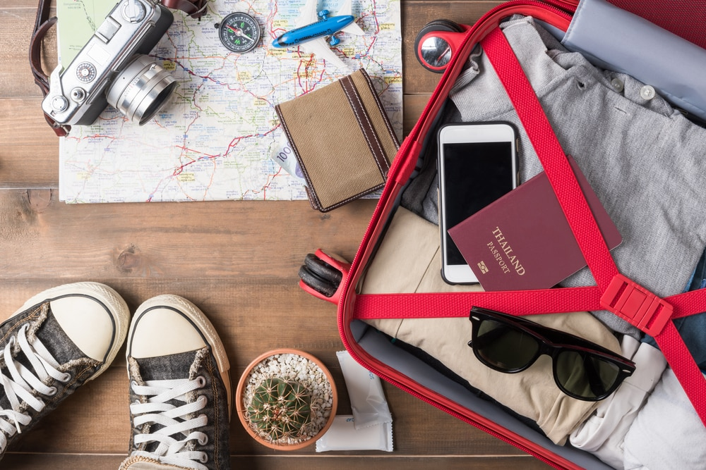Do I Need Travel Insurance? Is It Worth It? Holiday suitcase and travel items