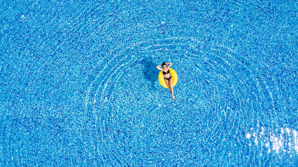 Travel Vaccinations Guide: Young woman relaxing on inflatable donut in swimming pool on holiday