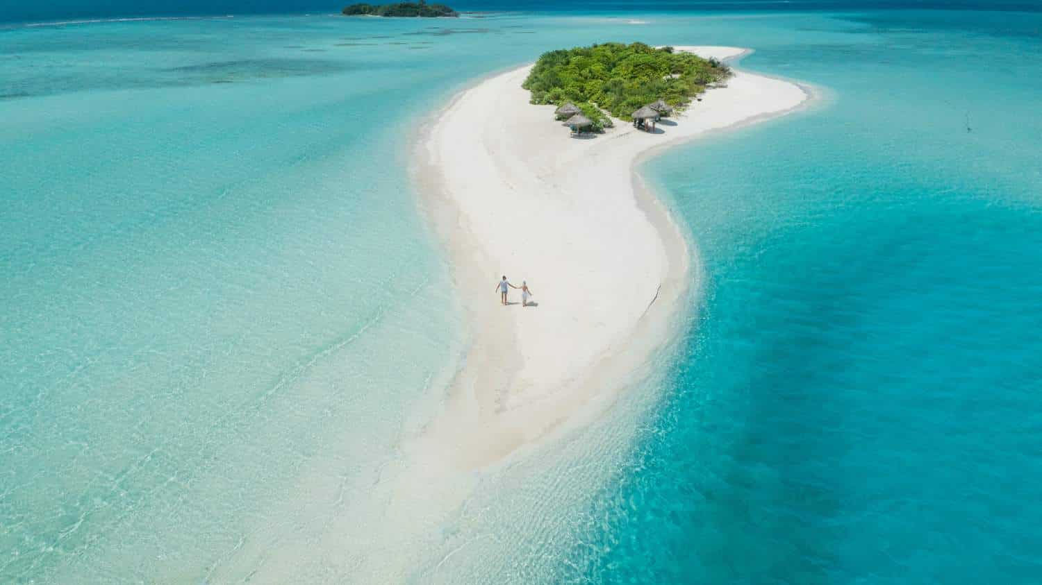 The worst destinations to fall ill on holiday: Drone picture of couple holding hands on island