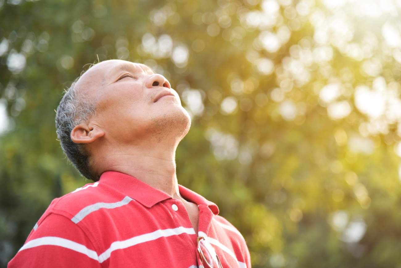 Senior man breathing in outside air