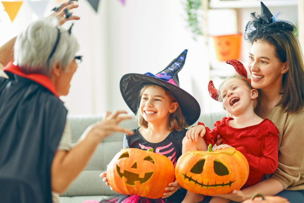 8 Spooky Destinations for a Halloween Holiday: grandmother dressed up for Halloween playing with grandchildren