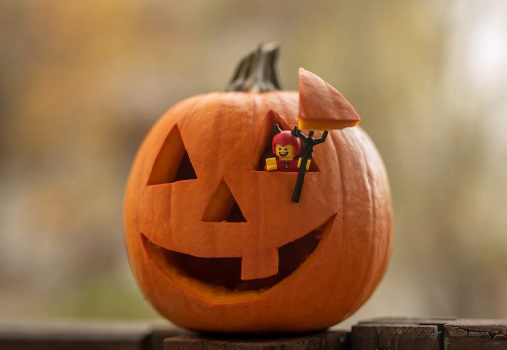 8 Spooky Destinations for a Halloween Holiday: Lego figure handing from Halloween pumpkin