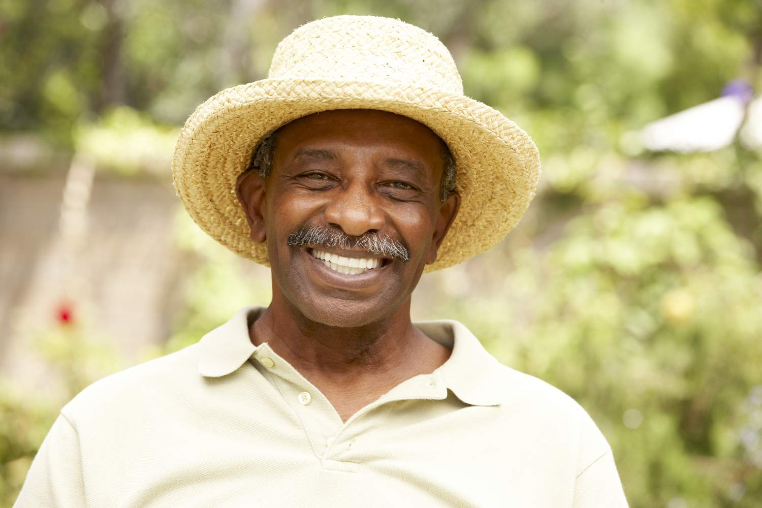 A happy mature man with a moustahce enjoying his holiday in a straw hat in a A Guide for Movember 2019