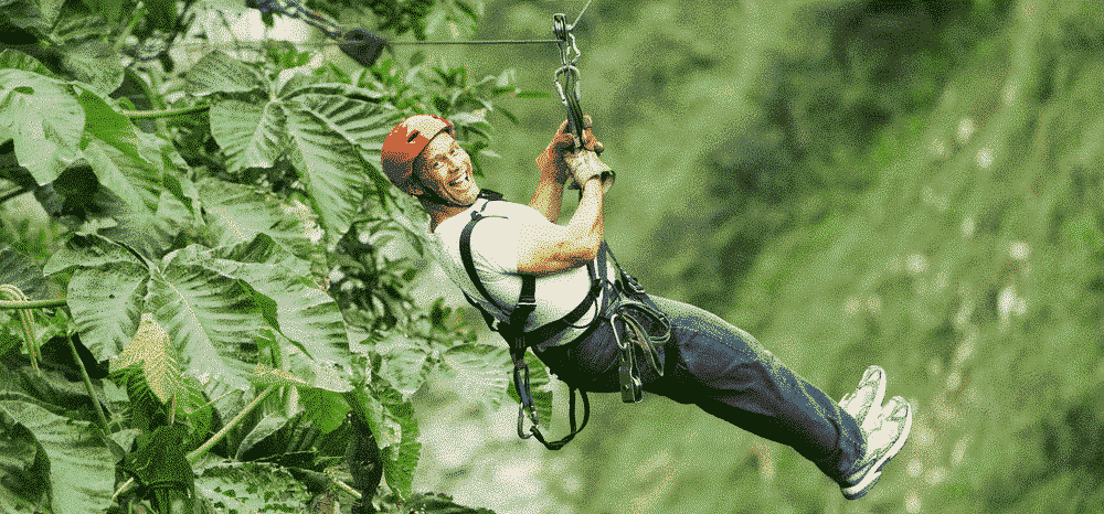 The 5 best ecotourism holidays for mature travellers: Man on zip wire through jungle