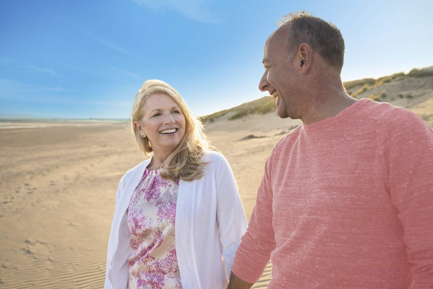 Mature happy couple on beach who have mental health travel insurance