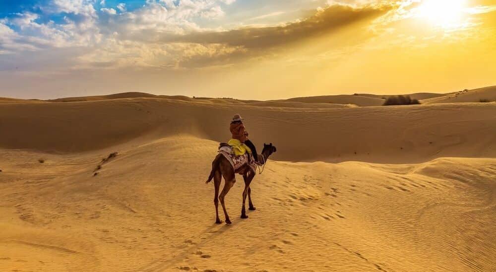 The-Best-Desert-Holiday-Destinations-on-Earth-camel-riding-through-the-Thar-Desert | AllClear Travel Blog