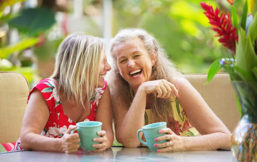Mature women friends laughing on holiday in our Top Tips for Travelling with COPD