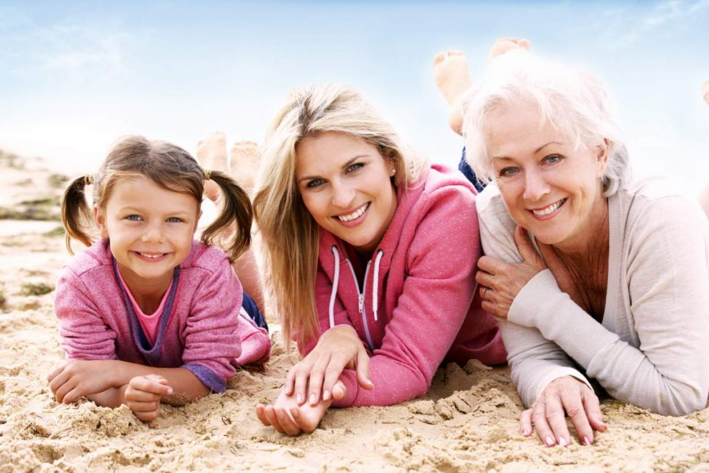 Travelling with breast cancer: grandmother, mother and daughter relaxing on the beach