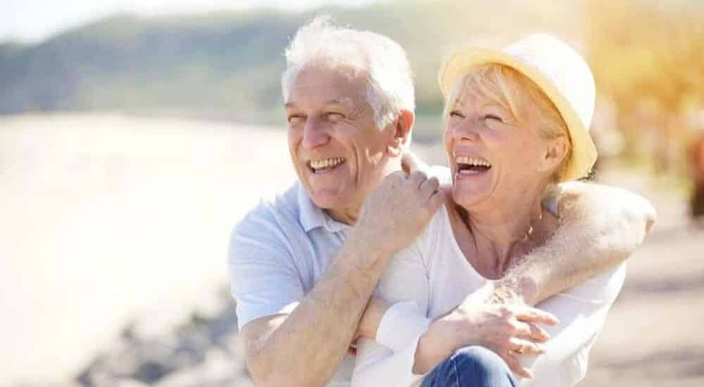 World-Alzheimers-Month-Couple-Laughing-at-the-Beach | AllClear Travel Blog