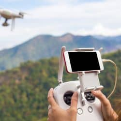 Best Holiday Gadgets / Covers Explained: Woman flying drone over jungle