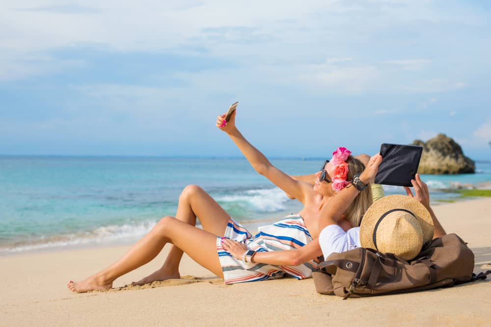 Best Holiday Gadgets / Covers Explained: Couple using tablet on the beach