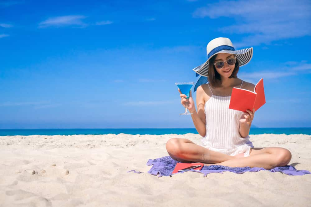 15 books to read on your holiday in 2019: Young woman reading book on beach with cocktail