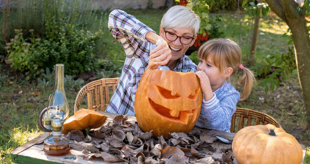 Most Popular Halloween Breaks & Destinations: grandmother and child pumpkin carving