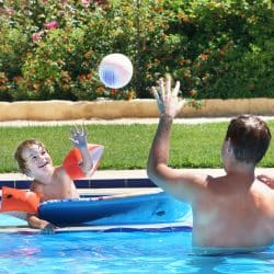 New study discovers how holidays help you live longer : Father and son playing in pool