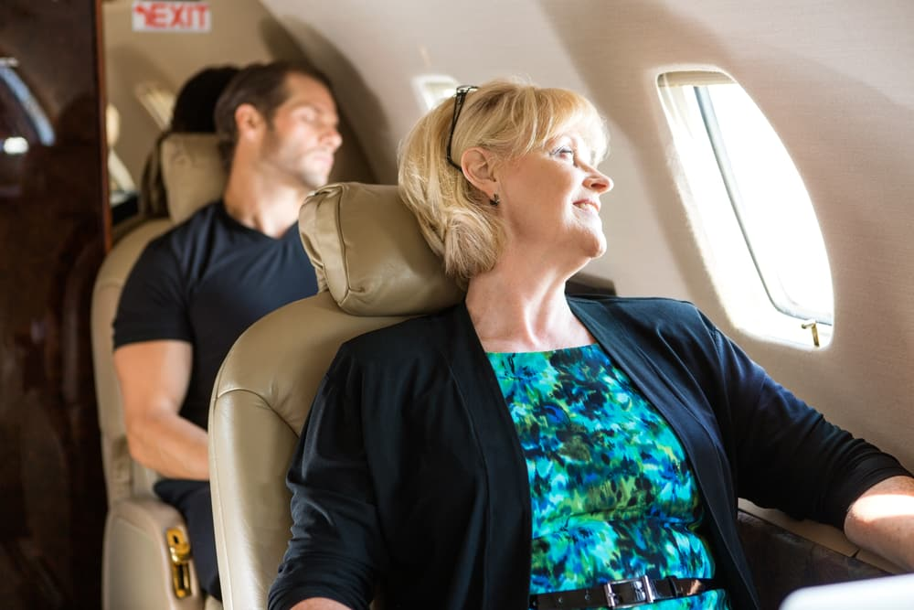 Do I Need Travel Insurance? Is It Worth It? Middle age woman looking out plane window