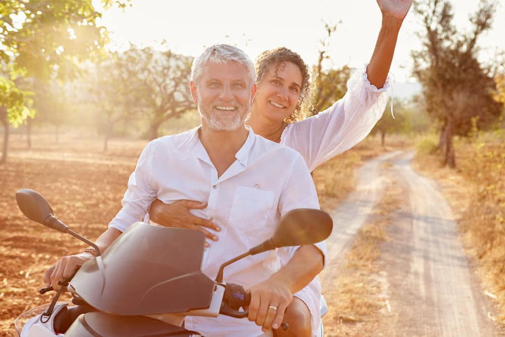 5 important questions to ask about your travel insurance: Mature couple riding motor bike on holiday