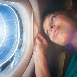 Preparing for a holiday with a medical condition: Young woman looking out plane window