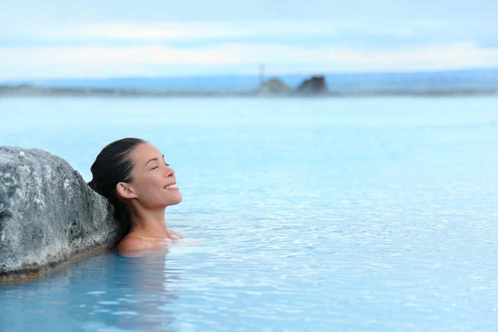 Travelling with a mental health condition: Young woman relaxing in hotspring, Iceland