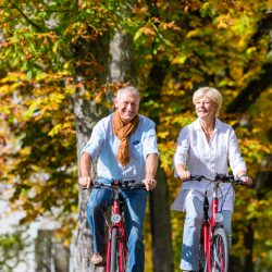 Do you need cycling holiday insurance? Middle aged couple cycling through forest in sun