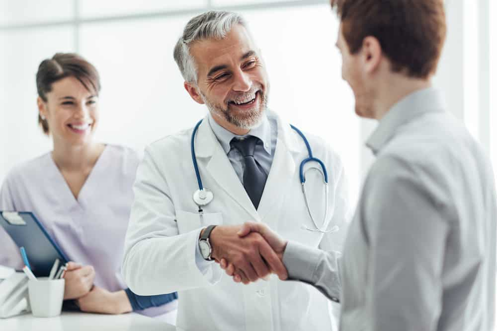 Do I Need Travel Insurance? Is It Worth It? Doctor shaking hands with patient