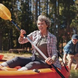 Travelling with a mental health condition: Happy middle aged woman kayaking