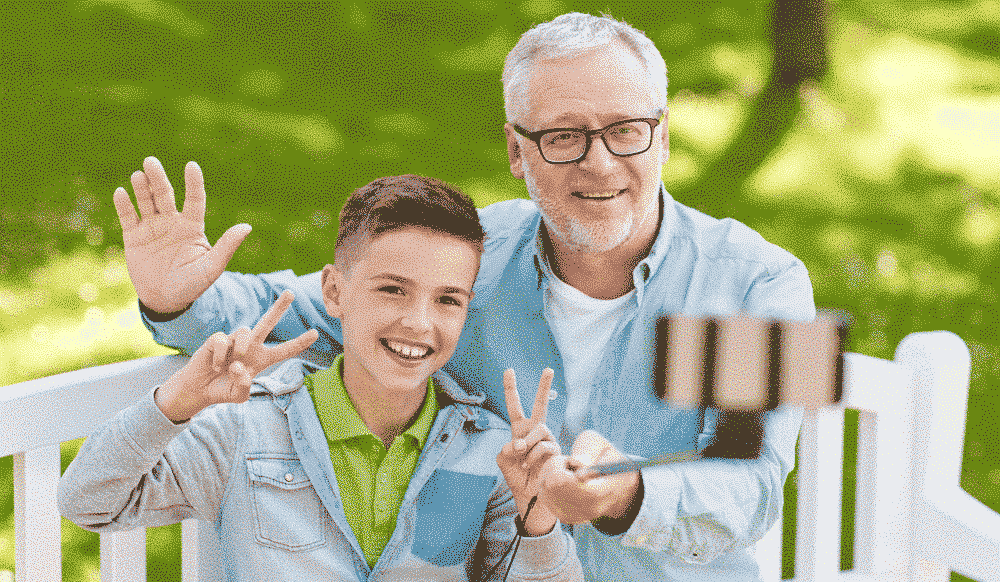 Best Holiday Gadgets / Covers Explained: Grandfather with child taking photo with selfie stick