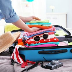 Travelling With Medications | Hand Luggage Restrictions: Woman packing her suitcase