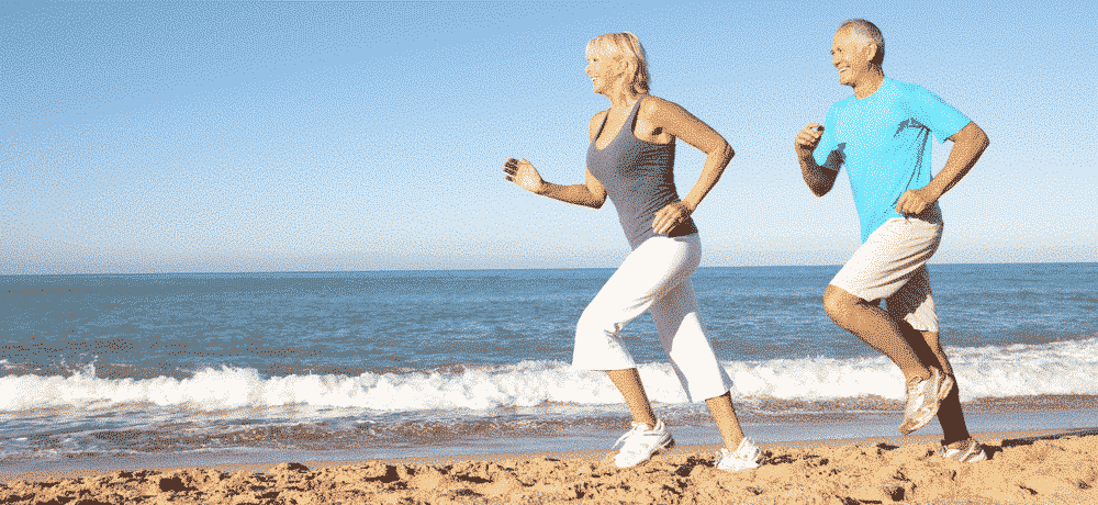 How to get fit when you are over 50: Mature man and woman running on beach