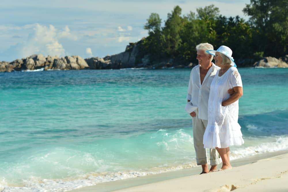 Holiday Curtailment Insurance: Senior couple on a beach