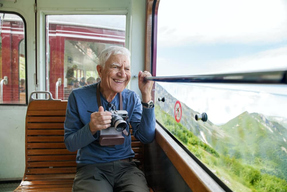 Medical Conditions That Prevent You From Flying: Old man on train taking photos