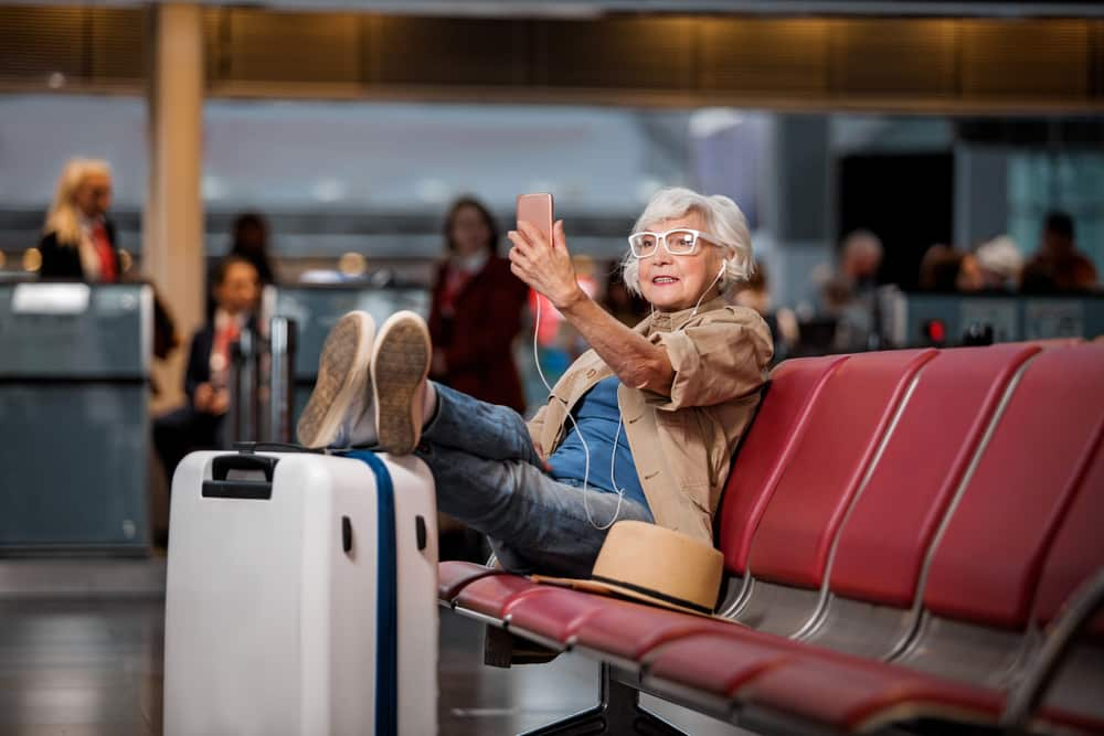 Can I Fly after a Stroke? Old woman sitting at the airport taking a selfie